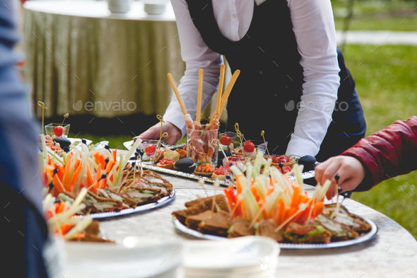 The waiter puts snacks on a buffet - Stock Photo - Images