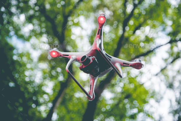 Drone with camera flying on green nature background - Stock Photo - Images