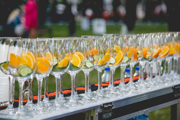 A row of glasses filled with ingredients for cucumber lemonade. - Stock Photo - Images