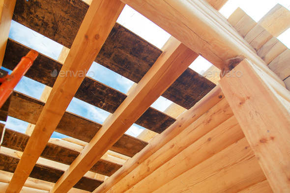 Wooden rafters against the blue sky in house under construction. - Stock Photo - Images
