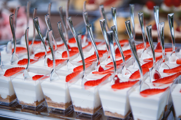 Portion cups with strawberries and cream for a buffet table. - Stock Photo - Images
