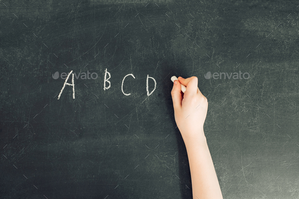 child's hand with chalk write alphabet on black chalkboard - Stock Photo - Images