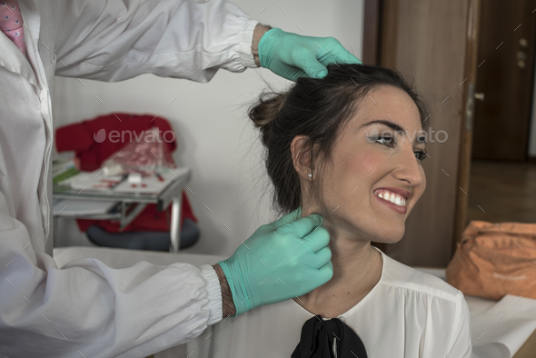 a doctor curing a bad cervical pain of a young girl  - Stock Photo - Images