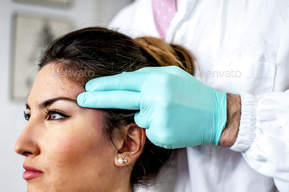 a doctor curing a bad cervical pain and headache of a young girl  - Stock Photo - Images