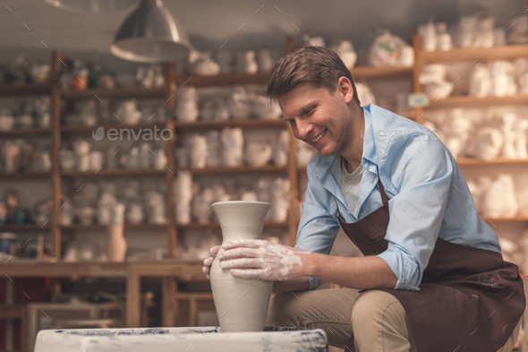 Young man at a potter's wheel indoors - Stock Photo - Images