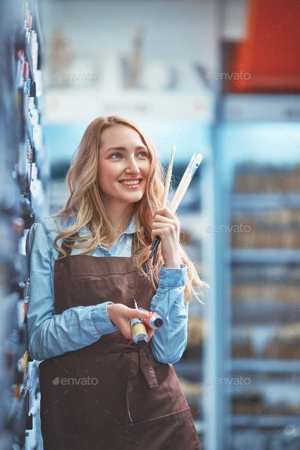 Smiling young girl in an apron - Stock Photo - Images