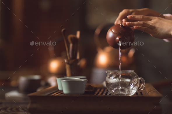 Female hands pouring tea from a teapot - Stock Photo - Images