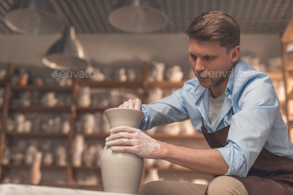 Young man at a potter's wheel - Stock Photo - Images