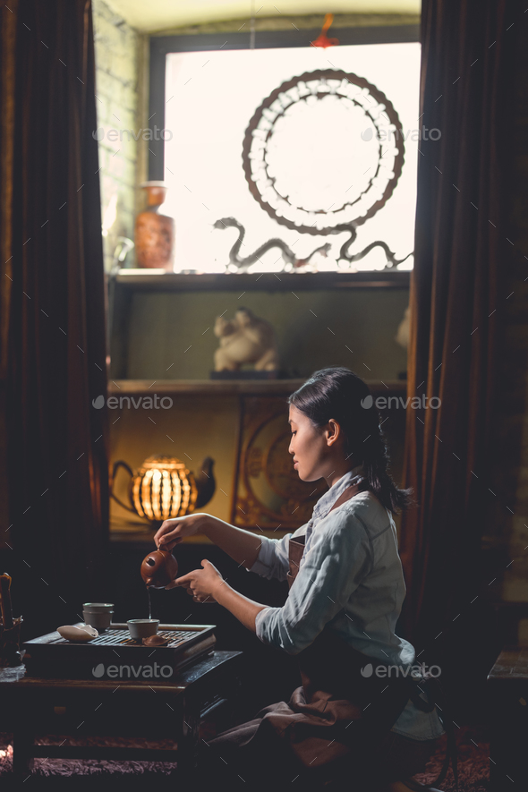 Young woman pouring tea from a teapot - Stock Photo - Images