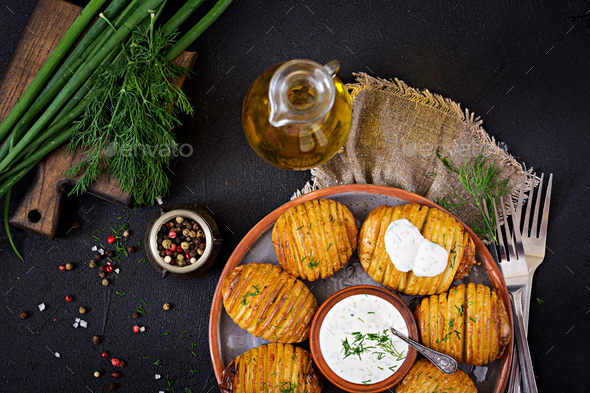 Baked potato with herbs and sauce on black background. Vegan food. Healthy meal. Top view. Flat lay - Stock Photo - Images