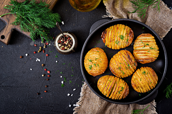 Baked potato with herbs on black background. Vegan food. Healthy meal. Top view. Flat lay - Stock Photo - Images