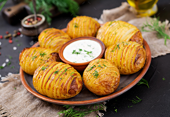 Baked potato with herbs and sauce on black background. Vegan food. Healthy meal. - Stock Photo - Images