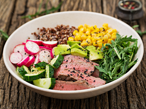 Buddha bowl lunch with grilled beef steak and quinoa, corn, avocado, cucumber and arugula - Stock Photo - Images
