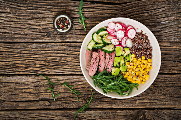 Buddha bowl lunch with grilled beef steak and quinoa, corn, avocado, cucumber  - Stock Photo - Images