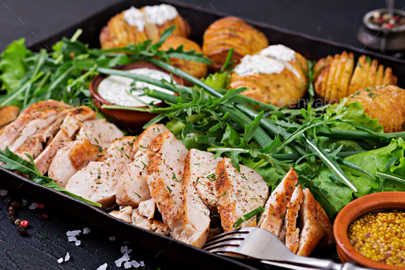 Chicken fillet cooked on a grill with a garnish of baked potatoes. Dietary meal. Healthy food. - Stock Photo - Images