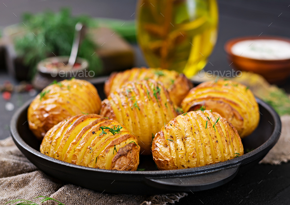 Baked potato with herbs on black background. Vegan food. Healthy meal. - Stock Photo - Images