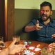 Funny photo of friends sitting at wooden table. Friends having fun while playing board game. - PhotoDune Item for Sale