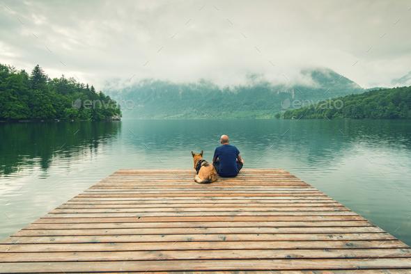 Man with dog sitting at wooden pier at Bohinj Lake, SLovenia - Stock Photo - Images