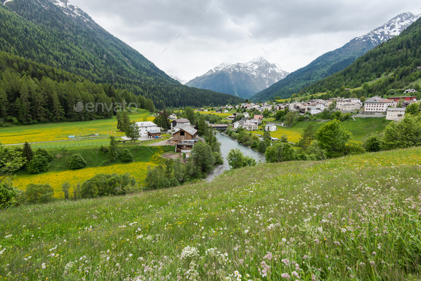 Village in valley in Switzerland at summer time - Stock Photo - Images
