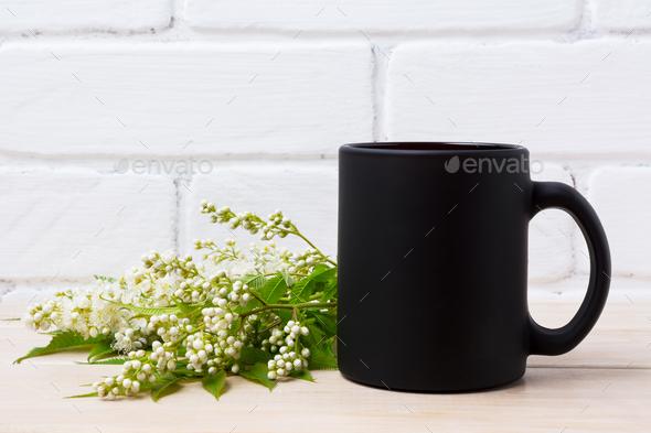 Black coffee mug mockup with white spiraea flowers - Stock Photo - Images