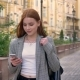 Young Beautiful Woman with Ginger Hair Walking in the City and Looking at Her Phone, Yellow Building - VideoHive Item for Sale
