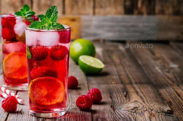 Raspberry Mojito Lemonade with lime and fresh mint in glass on wooden background - Stock Photo - Images