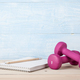 Fitness concept with pink dumbbells and notepad for workout plan - PhotoDune Item for Sale