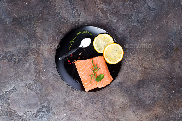 Salmon steaks on ice with lemon and salt on black plate. Lean proteins. - Stock Photo - Images