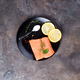 Salmon steaks on ice with lemon and salt on black plate. Lean proteins. - PhotoDune Item for Sale