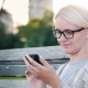 A Young Woman in Glasses Is Using a Smartphone. Sits on a Park Bench - VideoHive Item for Sale