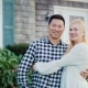 Portrait of a Happy Family on the Threshold of Their House. Asian Man and Caucasian Woman Hugging - VideoHive Item for Sale