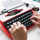 Woman hand working with bright red vintage typewriter - PhotoDune Item for Sale