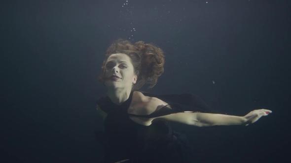 Woman In Black Dress Swimming Underwater In Pool On Dark