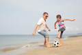 Father and son playing football on the beach at the day time. - PhotoDune Item for Sale