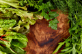 Mix leaf salad on wooden cutting board.