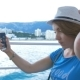 Woman in Hat Makes Selfie Bay with Yachts. Background Is the Town of Cremea - VideoHive Item for Sale