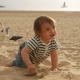 Child in a Striped T-shirt Runs Along the Beach with Sand By the Sea - VideoHive Item for Sale