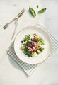 Fresh green summer salad with artichokes, olives and soft cheese