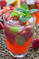 Homemade iced tea with strawberries and mint, vertical closeup