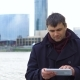 A Man with a Tablet on the Waterfront - VideoHive Item for Sale