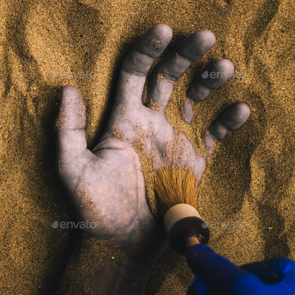 Forensic expert discovering dead body buried in desert sand - Stock Photo - Images
