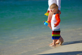 Two year old toddler walking on beach with mother - PhotoDune Item for Sale