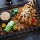 Close view of malaysian chicken skewers - satay or sate ayam with peanut sauce, dark background - PhotoDune Item for Sale
