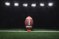 Football on tee under night lights