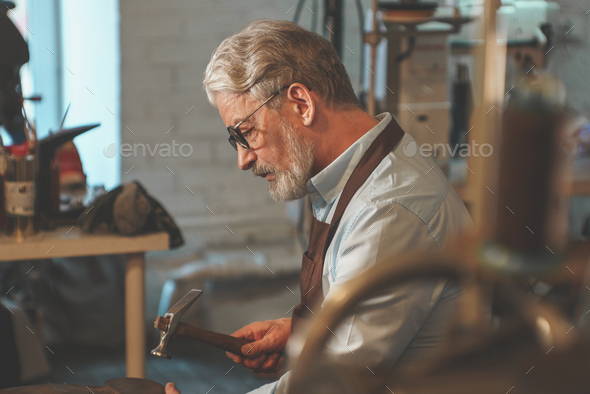 Elderly shoemaker in the workshop - Stock Photo - Images