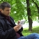 The Man Is Using a Tablet in the Park - VideoHive Item for Sale