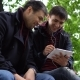 Two Young People Use a Tablet in the Park - VideoHive Item for Sale