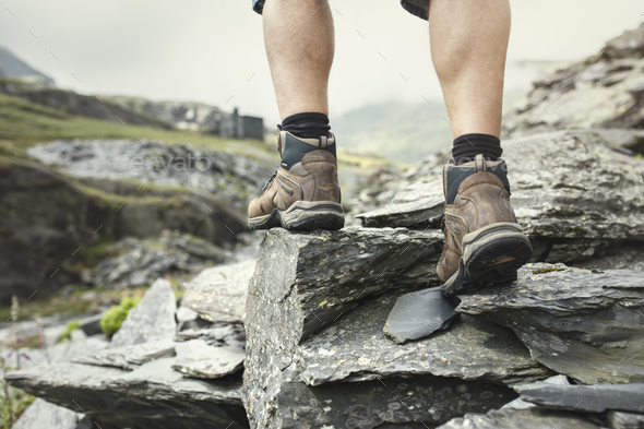 Hiking over rocks on a mountain trail - Stock Photo - Images