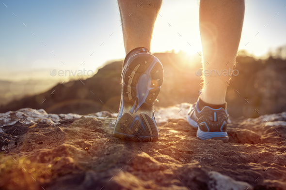 Runner feet running on trail looking at sunset - Stock Photo - Images