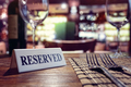 Reserved sign on restaurant table with bar background - PhotoDune Item for Sale